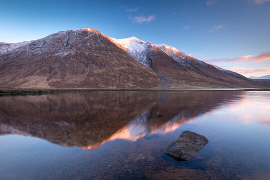Snow capped Highlands mountains reflected in the calm waters of Loch Etive in winter, Highlands, Scotland, United Kingdom
