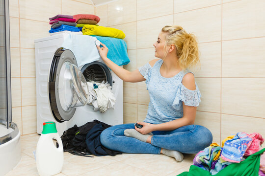Woman wash laundry using detergent pods