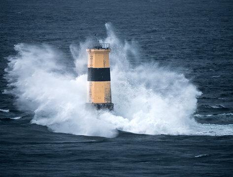 Waves crash on Tourelle de la Plate Lighthouse, Pointe du Raz, Finistere, Brittany, France