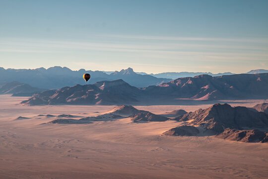 Rocky mountains, aerial view with hot air balloon flying over it, Namibia