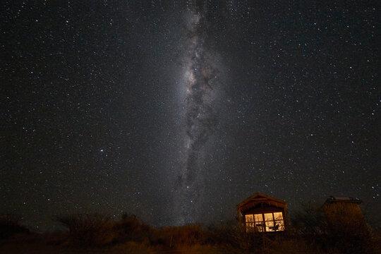 South hemisphere Milky Way and a small illuminated hut, Namibia