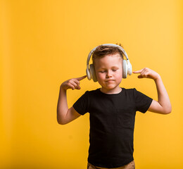 Fototapeta Technology and music concept. little kid boy with headphones listening to music against yellow background at home. Stylish kid boy