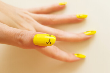 Acrylic Prints Manicure Close-up of female hand with yellow manicure and text smile on the nail