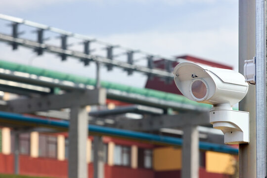 Security system of modern chemical factory petrochemical plant surveillance system CCTV camera operating to prevent theft accidents explosions catastrophes and industrial espionage, with copyspace.