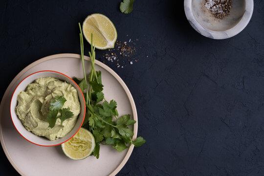 Avocado hummus dip on dark gray table, top view