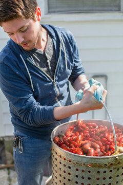 Caucasian man cooking crawfish outdoors