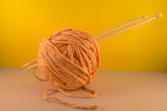 large pink ball for knitting with white knitting needles on a yellow background