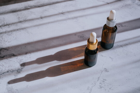 Cosmetic bottle made of dark glass on a light concrete surface. A spectacular long shadow comes from the bottle. Top view, minimalism, copy space. Natural organic vegan cosmetics concept.....
