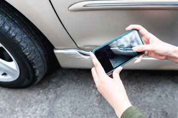 Obraz A woman using a mobile phone Take photos of the damage of the car, Which caused by a crash accident As evidence for insurance agents, to people and transportation insurance concept. - fototapety do salonu