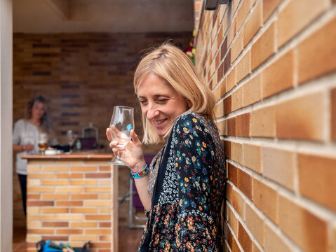 woman holding a glass of white wine while leaning against a wall in her backyard