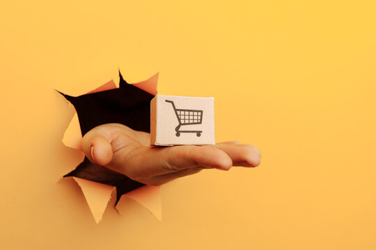 Hand with a box through a yellow paper hole. Delivery concept