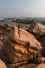 Skalne wybrzeże na tle oceanu, fal i palm o zachodzie słońca.