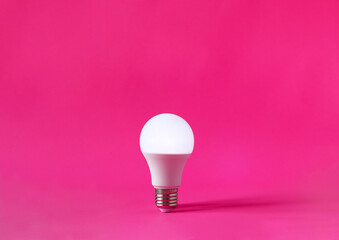 Obraz Glowing light bulb on magenta background. Discovery, invention, new idea concept. - fototapety do salonu