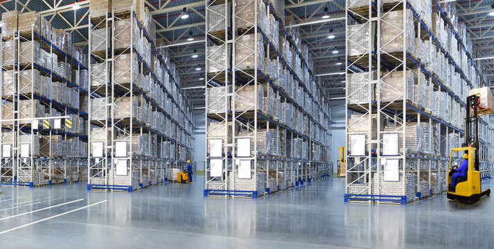 Huge distribution warehouse with high shelves and forklifts.