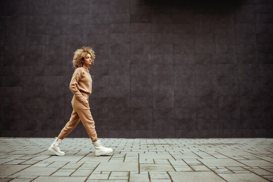 Side view of trap girl in tracksuit walking with hands in her pockets and listening music.