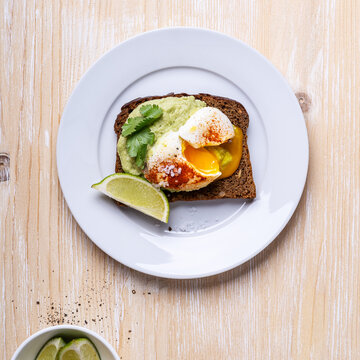 Poached egg on smashed avocado on brown toast served on white plate