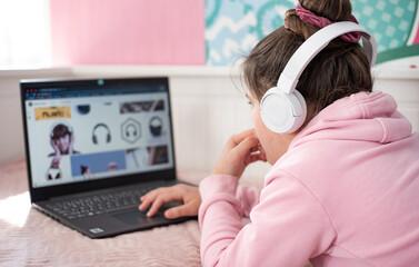 Fototapeta girl, children, computer, laptop, cyberspace web Nastoletnia uczennica dziewczyna w słuchawkach studiuje w domu i robi notatki. Nastoletni student na odległość uczenia się na laptopie, odrabianie lekc obraz