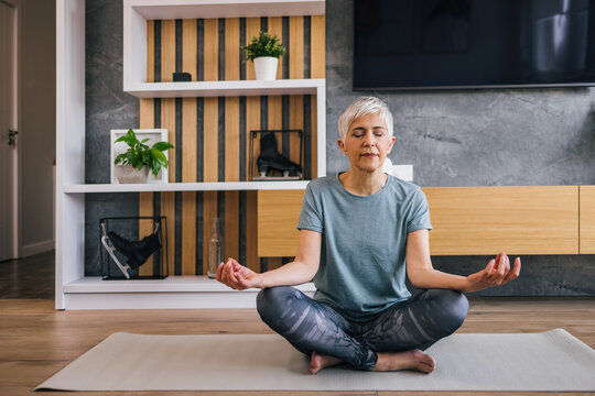 Senior woman sitting in lotus pose on yoga mat meditating at home.