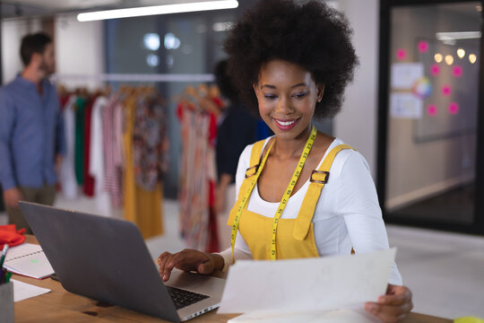 American woman fashion designer wearing tailor's tape measure holding document using laptop