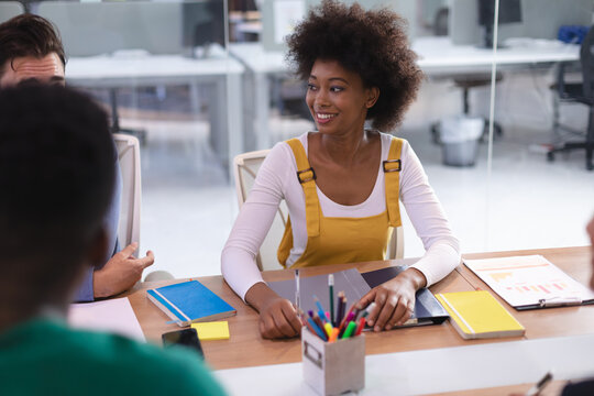 Happy african american businesswoman sitting at desk in meeting room listening colleagues