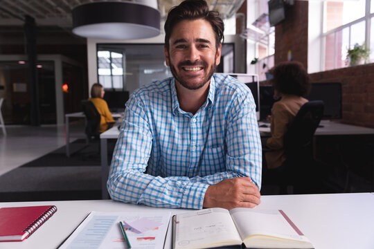 Caucasian businessman sitting at desk with documents having video call smiling