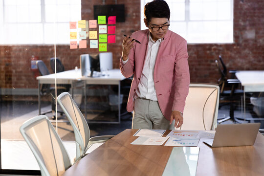 Stylish asian businessman having conversation standing by desk using smartphone