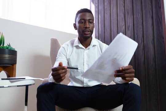 Casual african american businessman holding pen and document sitting in armchair
