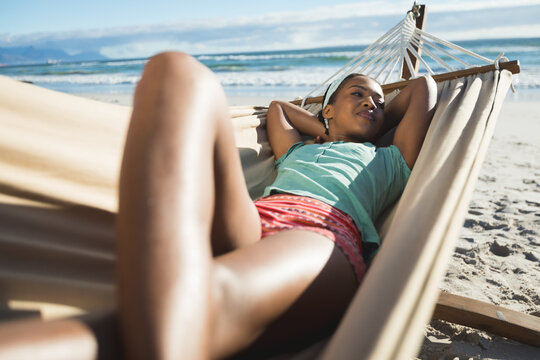 Happy african american woman laying in hammock on the beach