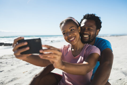 Happy african american couple on beach by the sea taking selfie