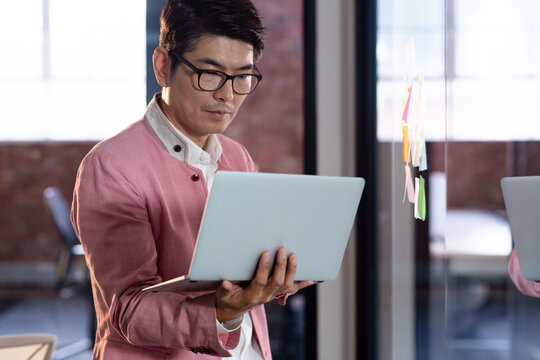 Stylish asian businessman standing and using laptop computer