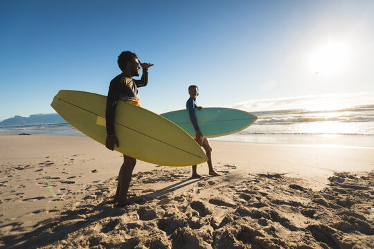 Happy african american couple on the beach carrying surfboards