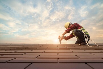 Obraz Roofer working in special protective work wear gloves, using air or pneumatic nail gun installing concrete or CPAC cement roofing tiles on top of the new roof under construction residential building - fototapety do salonu