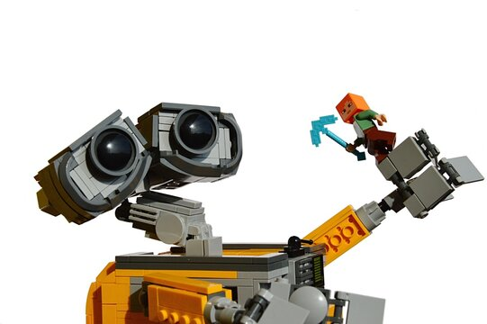 LEGO Wall-E robot holding small LEGO Minecraft Alex figure with diamond pickaxe, balancing on his left arm, white background.
