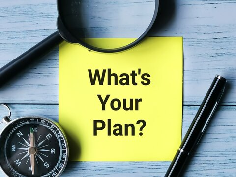 Text What is your plan written on sticky note with a pen,compass and magnifying glass.