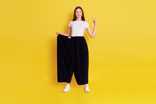 Cocky European woman with dark hair, wearing white t shirt and old too big pants, loosing weight, showing rock sing, looking at camera with excited expression, isolated over yellow background.