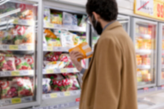 A masked man in a supermarket selects an item in the freezer section. Blurred. Coronavirus pandemic.
