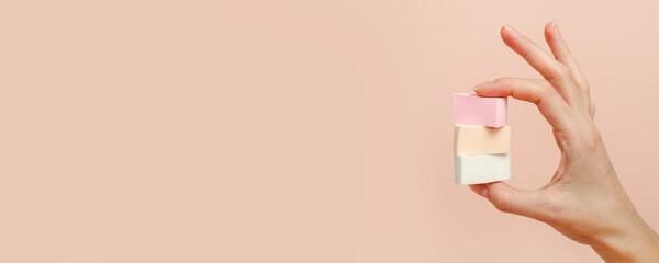 Cosmetic sponge beauty blender in woman hand on a beige background, modern trendy still life,...