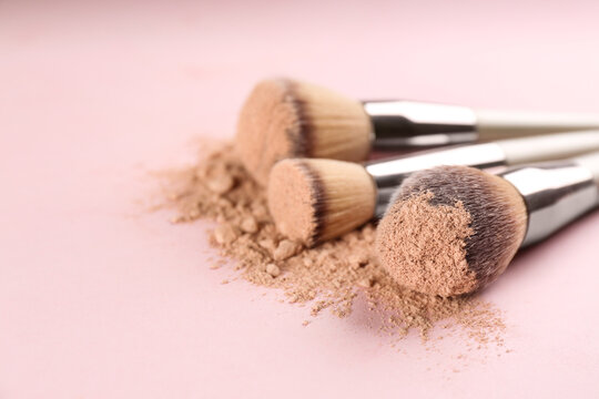 Different makeup brushes with crushed cosmetic product on pink background, closeup. Space for text