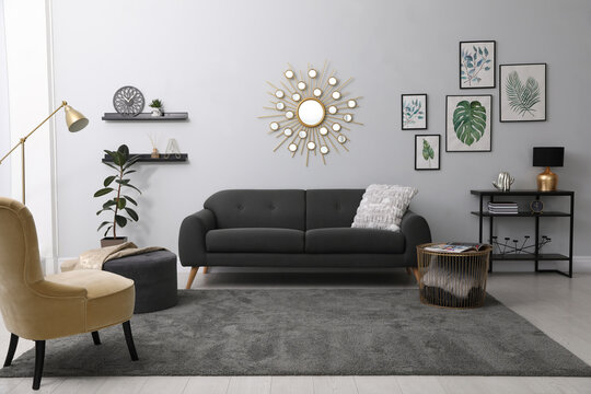Stylish living room interior with comfortable sofa and floral pictures