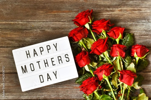 light box with the text HAPPY MOTHER'S DAY and red roses on a wooden background. The concept of the holiday.