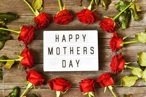 A light box with the inscription HAPPY MOTHER'S DAY and red roses are laid out in a circle on a wooden background. The concept of the holiday.