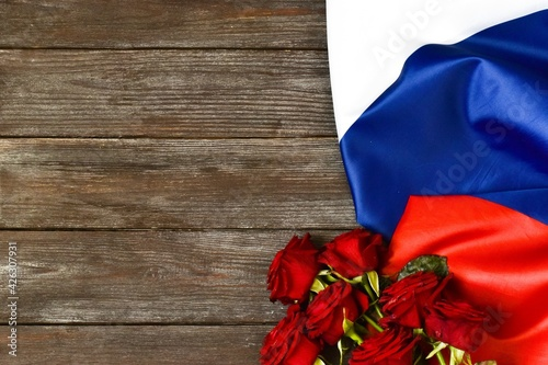 Russia day is a Russian holiday. June 12 Day of Russia. Bouquet of red roses and the flag of Russia on a wooden background. Copy space, flat lay.