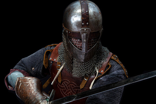 Young man in knight armor on black background