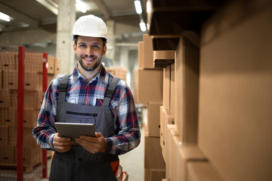 Portrait of warehouse supervisor holding tablet computer and standing by cardboard boxes with goods in factory storage room.