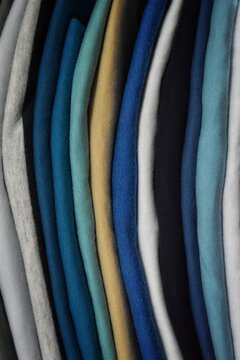 Bedding is in the closet on the shelf. Towels folded in a roll. On hangers hanging ladies' and men's clothing.