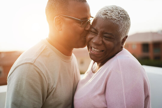 Happy african couple having tender moment outdoors at summer sunset time - Focus on woman face