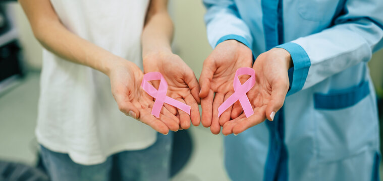 Two women showing cancer awareness medical stick ribbon for the healthcare of female breast and prevention of cancer