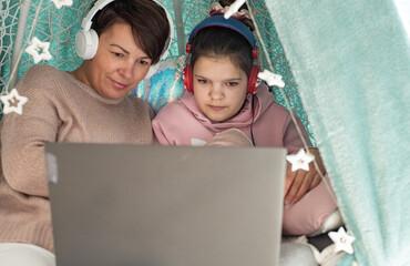 Obraz Mama i córka razem, praca i nauka zdalna na laptopie, wspolne spędzanie czasu mamy z dzieckiem, pomoc dziecku w nauce - fototapety do salonu