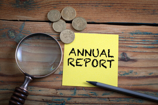 Annual Report. Note paper, cash and magnifying glass on a wooden table