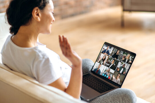 Remote work, online communication. A pregnant woman uses a laptop, communicates with colleagues by video call while sitting at home on the sofa, greets the interlocutors with a hand gesture, smiles